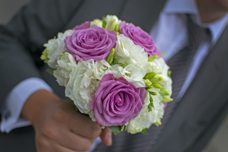 Man or groom holding an elegant bouquet or bunch of flowers