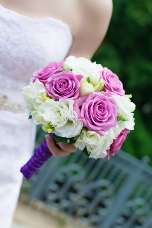 Elegant hand-tied bouquet of flowers in the hand of a bride