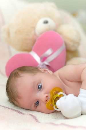 Infant baby  5 weeks old  lying on bed with teddy bear photo