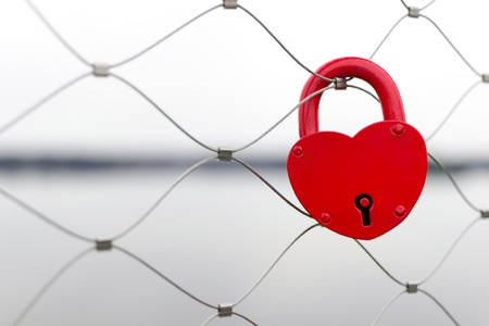 Red love padlock on bridge fence - wedding day tradition  Shallow depth of field Stock Photo