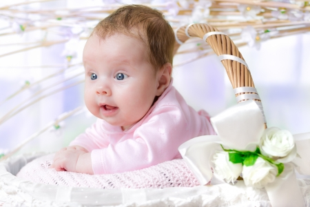 sallow: 3 months old happy baby girl in a decorated wicker basket