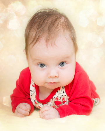 4 months old baby girl on a glitter bokeh background Stock Photo