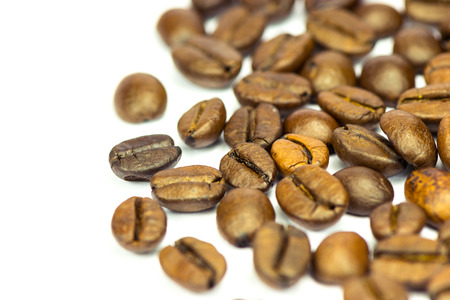 PIle of fine selected roasted coffee beans on white background  Shallow depth of field photo