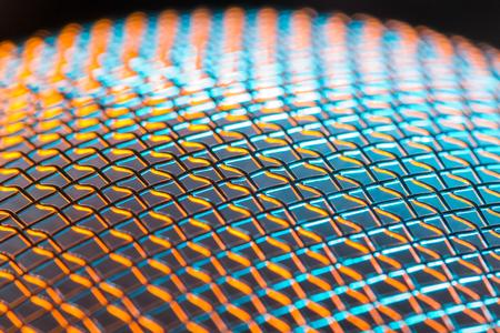 metal grid: Steel net sphere lit in blue and orange  Shallow depth of field