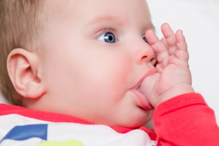 six months: Six months old baby sucking thumb - teething Stock Photo