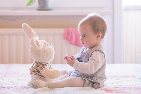 10 months old baby girl playing with plush rabbit Standard-Bild
