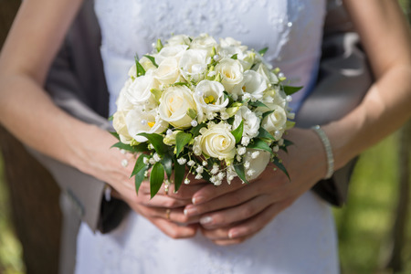 Wedding bouquet held by bride and groom  Shallow depth of field Stock Photo