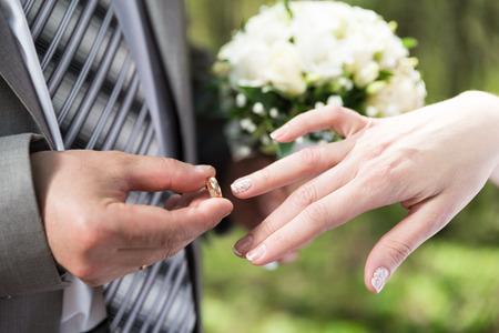 put: Wedding day  Groom putting ring on bride s finger