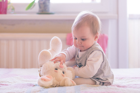 10 months old baby girl playing with plush rabbit Stock Photo