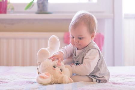 meses del año: Niña de 10 meses de edad bebé jugando con el conejo de peluche Foto de archivo