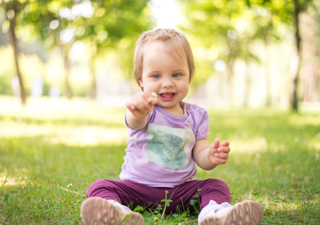 Happy 1 year baby girl holding a flower while sitting on grass in a park. Shallow depth of field