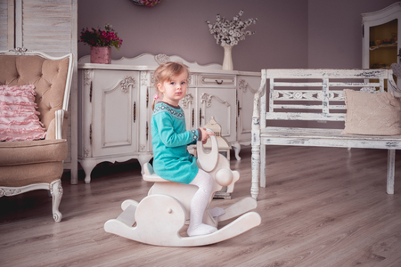 Little girl in a provence interior riding a rocking rabbit