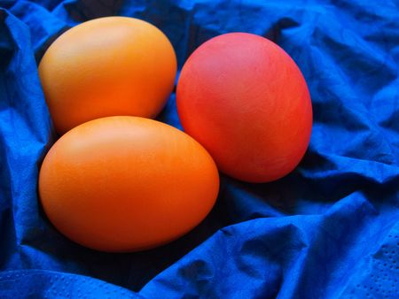 arisen: three painted easter eggs on the bright blue serviette