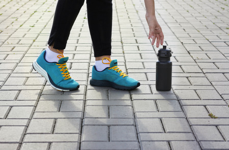 strive: Young girl in sneakers reaching for a bottle Stock Photo
