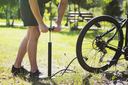 Inflating the tire of a bicycle. Cyclist repairs bike in forest. Bicyclist pumping air into the wheel. Biker uses a bicycle pump. Pumping air into an empty wheel of bike.