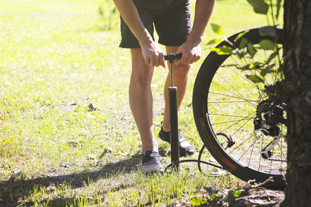 inflating: Inflating the tire of a bicycle. Cyclist repairs bike in forest. Bicyclist pumping air into the wheel. Biker uses a bicycle pump. Pumping air into an empty wheel of bike.