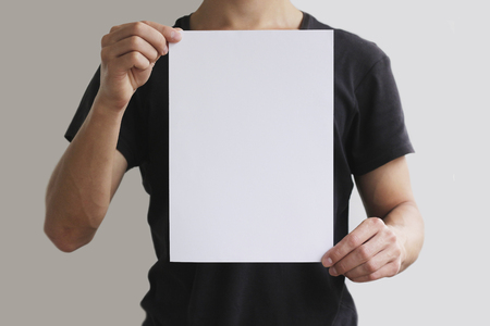 vertically: Man holding white A4 paper vertically