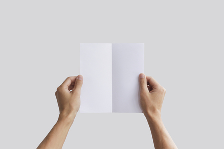 pamphlet: Hand holding blank brochure booklet in the hand. Leaflet presentation. Pamphlet hand man. Man show offset paper. Sheet template. Book in hands. Booklet folding design. Fold paper sheet display read.