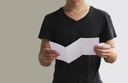 pamphlet: Man reading blank white flyer brochure booklet. Leaflet presentation. Pamphlet hold hands. Man show clear offset paper. Sheet template.