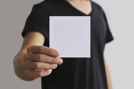 Man showing blank white square flyer brochure booklet. Leaflet presentation. Pamphlet hold hands. Man show clear offset paper. Sheet template. Booklet design sheet display read first person Archivio Fotografico