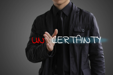 The concept of certainty. Businessman making certainty from unce Фото со стока