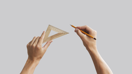 isolated on grey: Hands hold the pencil with triangular wooden ruler. Isolated grey.
