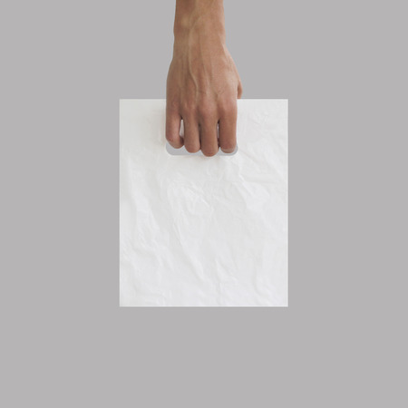 Blank plastic bag mock up holding in hand. Empty polyethylene package mockup hold in hands isolated on grey.