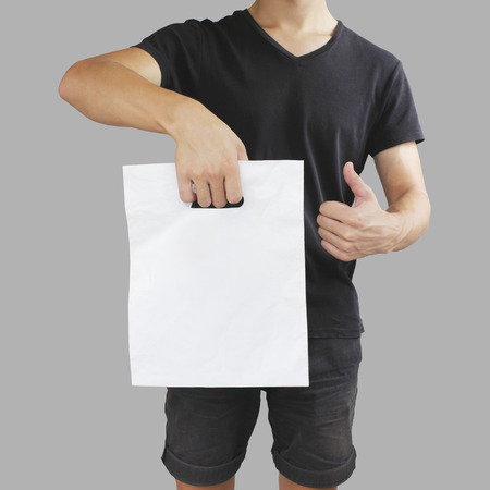 Man shows blank plastic bag mock up and thumb up isolated.