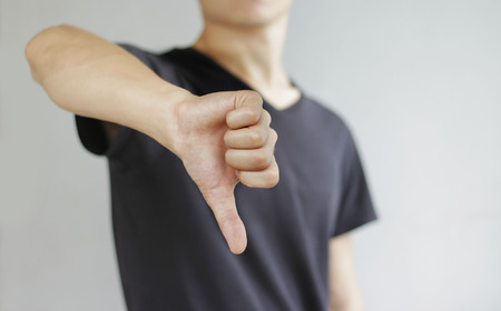 unsatisfied: Young man in black t shirt showing a sign of dislike, isolated on a gray background. Stock Photo