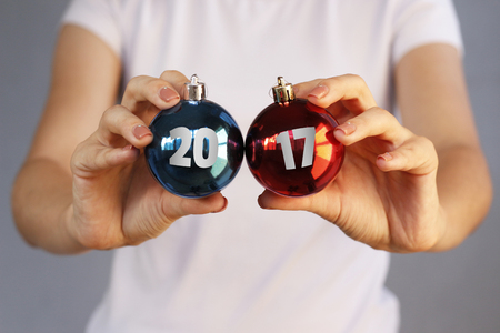 17 20: Girl in white t-shirt holding Christmas toy two ball with inscription 2017. Red, blue.