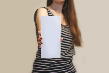 show of hands: Girl showing blank white flyer brochure booklet. Leaflet presentation. Pamphlet hold hands. Woman show clear offset paper. Sheet template. Booklet design sheet display read first person