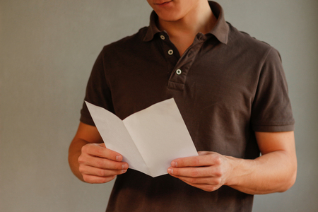 offset views: Man reading blank white flyer brochure booklet. Leaflet presentation. Pamphlet hold hands. Man show clear offset paper. Sheet template.