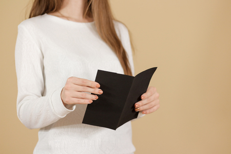 offset views: Girl reading blank black flyer brochure booklet. Leaflet presentation. Pamphlet hold hands. Woman show clear offset paper. Sheet template. Booklet design sheet display read first person Stock Photo