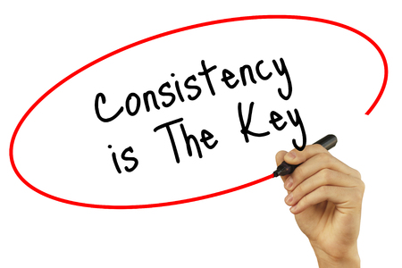 consistency: Man Hand writing Consistency is The Key with black marker on visual screen. Isolated on white background. Business, technology, internet concept. Stock Photo