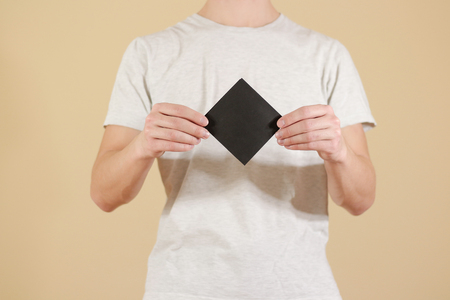 note booklet: Man showing blank black square flyer brochure booklet. Leaflet presentation. Pamphlet hold hands. Man show clear offset paper. Sheet template. Booklet design sheet display read first person Stock Photo