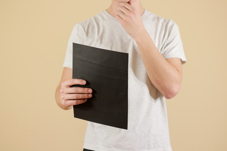 offset up: Man holding black A4 paper. Read booklet. Leaflet presentation. Pamphlet hold hands. Man show clear offset paper. Sheet template. Booklet design sheet display read first person Stock Photo
