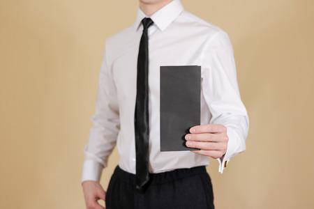 offset views: Man showing blank black flyer brochure booklet. Leaflet presentation. Pamphlet hold hands. Man show clear offset paper. Sheet template. Booklet design sheet display read first person