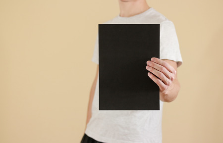 offset views: Man holding black A4 paper vertically. Leaflet presentation. Pamphlet hold hands. Man show clear offset paper. Sheet template. Booklet design sheet display read first person