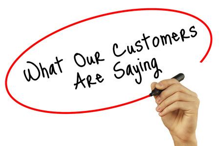 Man Hand schrijven Wat onze klanten zeggen met zwarte stift op visuele scherm. Geïsoleerd op achtergrond. Business, technologie, internet concept. Stock foto Stockfoto