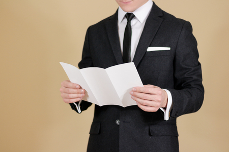 offset views: Man showing blank black flyer brochure. Read detailed booklet. Leaflet presentation. Pamphlet hold hands. Man show clear offset paper. Sheet template. A man in a black suit, white shirt and tie. Stock Photo