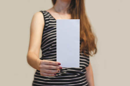 offset views: Girl showing blank white flyer brochure booklet. Leaflet presentation. Pamphlet hold hands. Woman show clear offset paper. Sheet template. Booklet design sheet display read first person