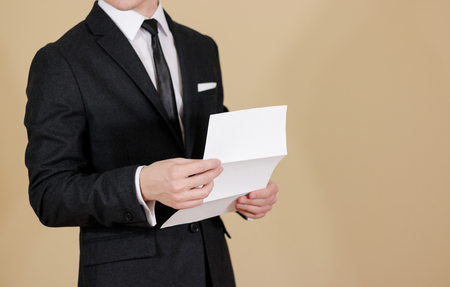 offset up: Man showing blank black flyer brochure. Read detailed booklet. Leaflet presentation. Pamphlet hold hands. Man show clear offset paper. Sheet template. A man in a black suit, white shirt and tie. Stock Photo
