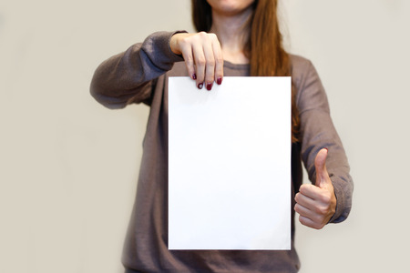 offset views: Girl holding white A4 blank paper vertically and thumbs up. Leaflet presentation. Pamphlet hold hands. Woman show clear offset paper. Sheet template. Booklet design sheet display read first person.