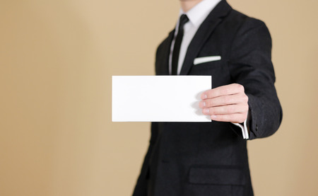 Man showing blank black flyer brochure booklet. Leaflet presentation. Pamphlet hold hands. Man show clear offset paper. Sheet template. Man in a black suit, white shirt and tie.