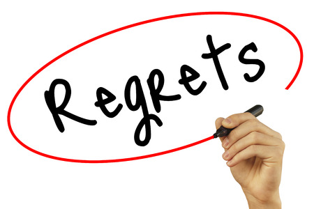 Man Hand writing Regrets with black marker on visual screen. Isolated on background. Business, technology, internet concept. Stock Photo