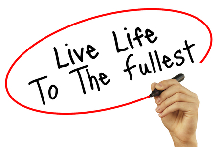 Man Hand writing Live Life To The Fullest with black marker on visual screen. Isolated on background. Business, technology, internet concept. Stock Photo
