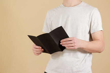 offset views: Man showing blank black flyer brochure. Read detailed booklet. Leaflet presentation. Pamphlet hold hands. Man show clear offset paper. Sheet template. Booklet design sheet display read first person Stock Photo