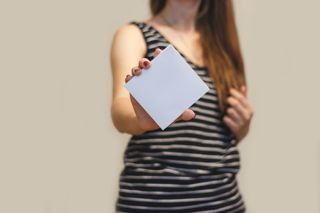 offset up: Girl showing blank white square flyer brochure booklet. Leaflet presentation. Pamphlet hold hands. Woman show clear offset paper. Sheet template. Booklet design sheet display read first person Stock Photo
