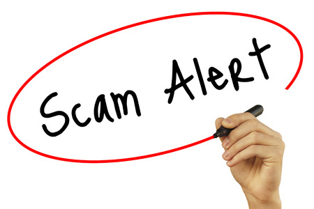 Man Hand writing Scam Alert with black marker on visual screen. Isolated on background. Business, technology, internet concept. Stock Photo
