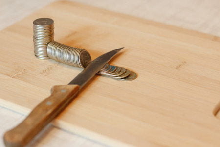 price cutting: Knife cutting a pile of coin. Concept of budget cuts, savings, recession. The division into parts. Taxes. Interest rate.